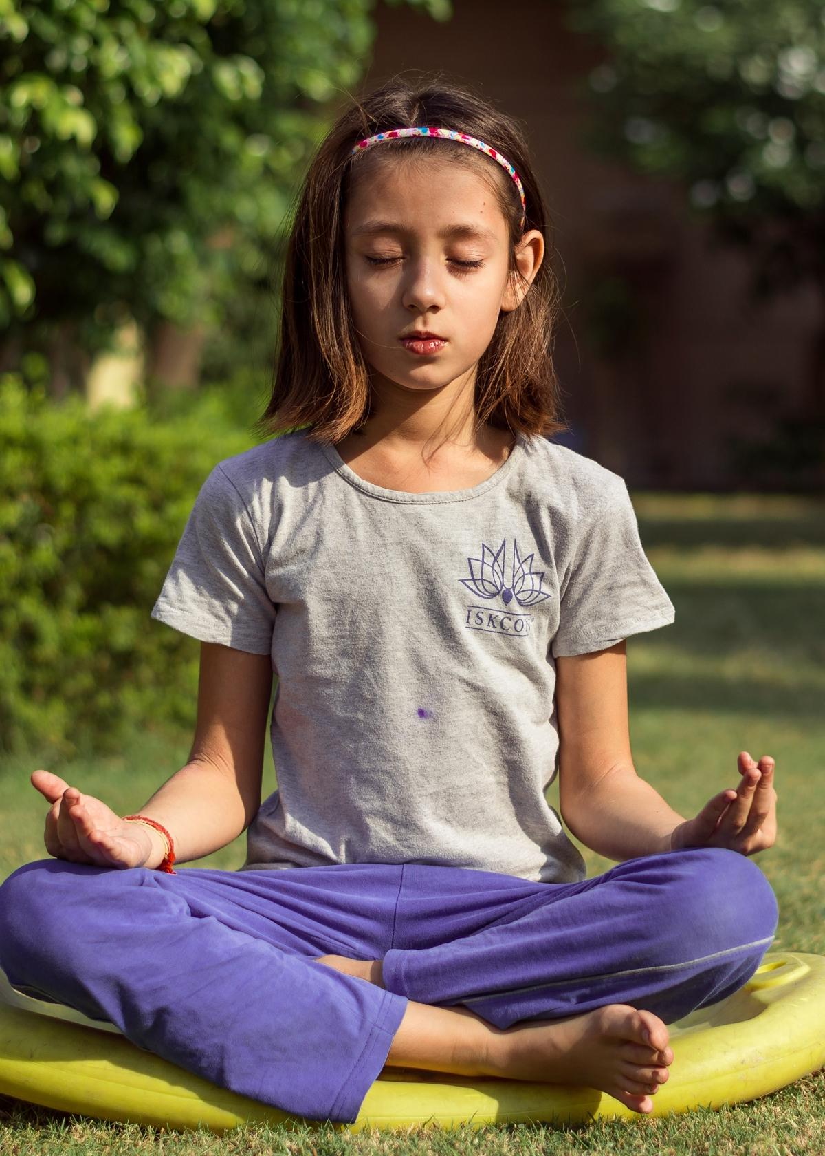 Kind mediteert in een yogahouding in jnana mudra