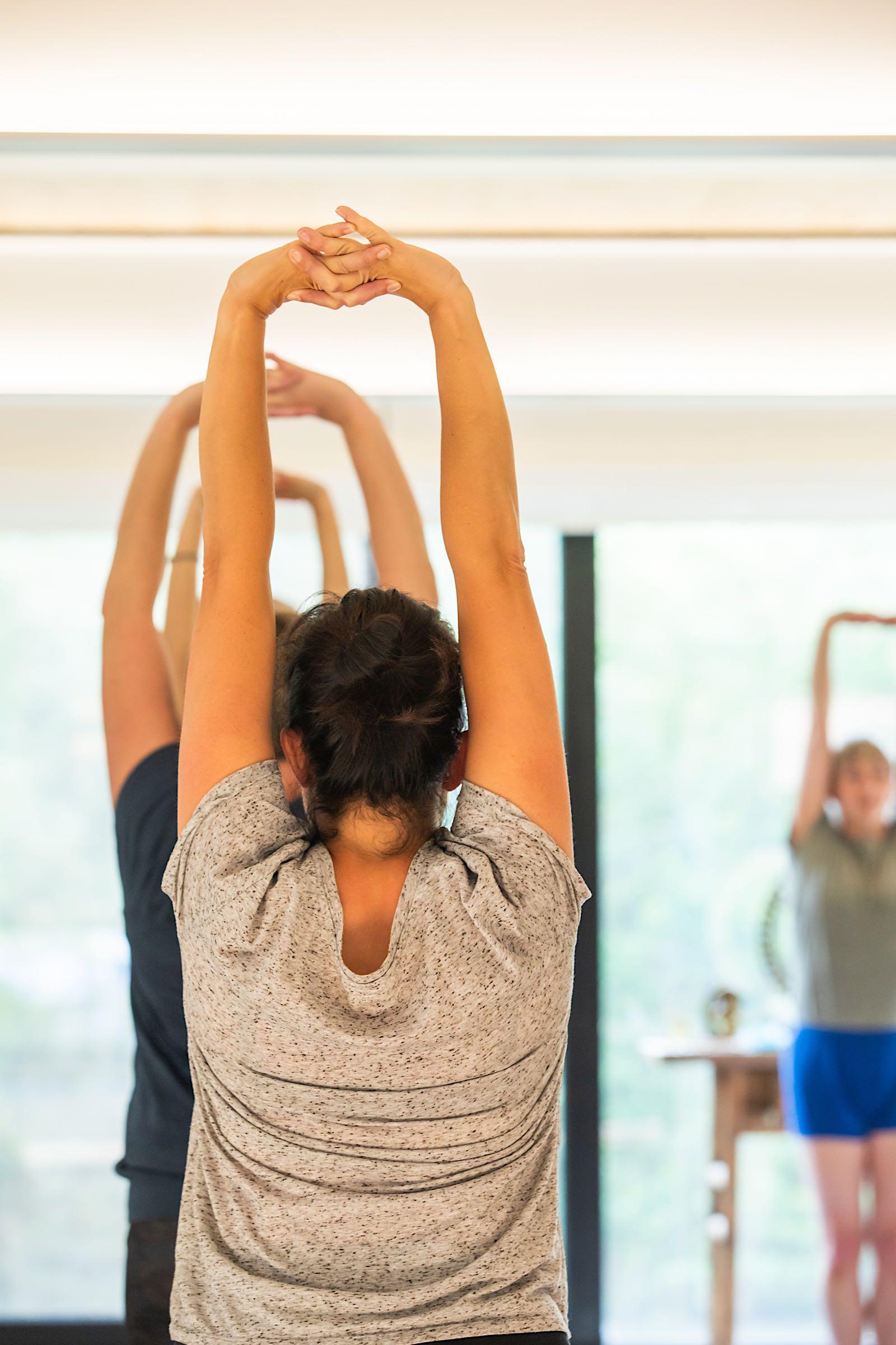 Yogi's oefenen baddhanguliyasana in tadasana in yogastudio Bornem